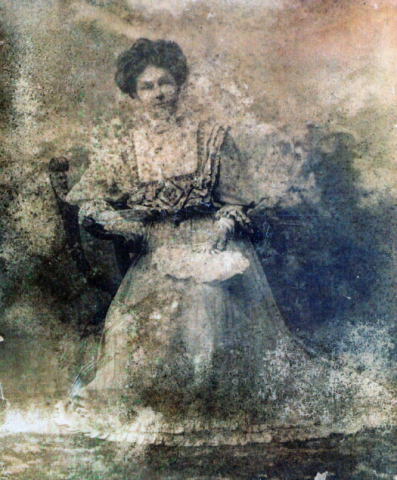 Faded worn black and white photograph of Annie Combellack