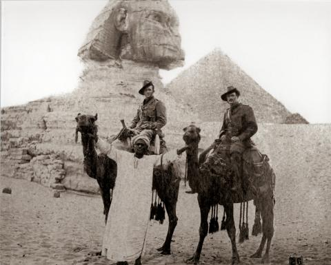 Image depicts Chamberlain on a camel with sphinx and pyramids as backdrop.