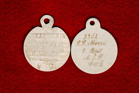 Worn rounded identity tags of Reginald Morris.