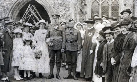 Black and white photograph of a group of people, men in uniform and women in dress clothes.