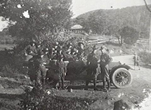 Black and white photo of soldiers gathered around a motor car.