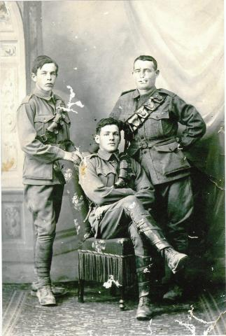 Black and white photo of three soldiers in uniform.