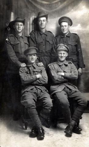 Black and white portrait of five men in uniform.