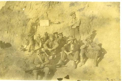 Faded sepia photograph of soldiers in uniform outdoors.