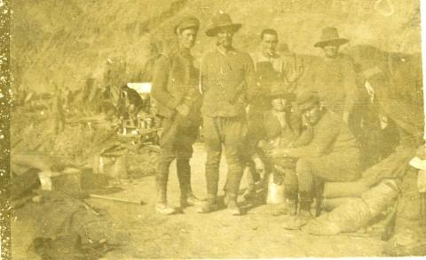 Sepia faded photograph of soldiers in uniform outdoors.
