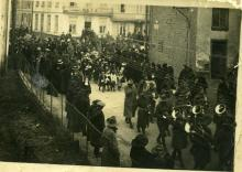 Front of poscard. Sepia image of soldiers and people on the street.