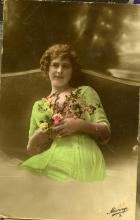 Woman in a green dress holding flowers