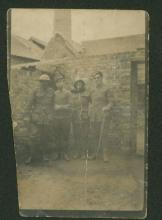 Faded sepia photograph of four men in uniform.