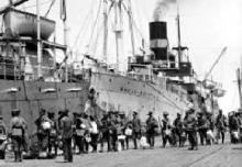 Black and white photograph of soldiers boarding a ship.