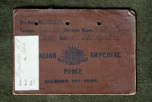 Image depicts leather-bound brown pay book.