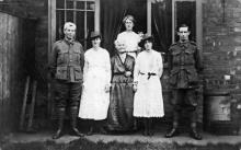Black and white photograph of five people, three women two men. Men in uniform and women in white dresses.
