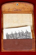 Worn leather-like wallet with a black and white photograph of men in uniform inside.
