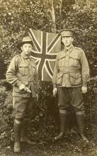 Sepia photo of Arthur Smith and friend posing in front of the Union Jack