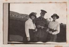 Photograph of man in uniform and two women on each side of him.