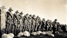 Sepia photograph of soldiers in uniform standing in a line.