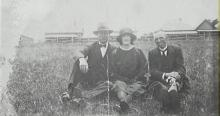 Black and white photo of three people posing, outdoors.